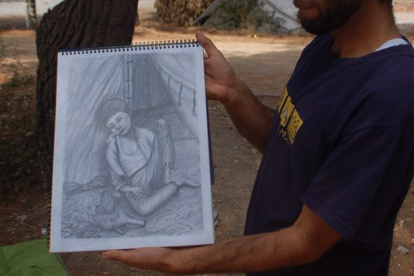 Dilgin displays his drawing of a child in the camp. (Iris Samuels)