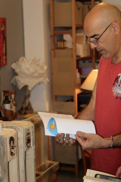 Aiora founder Aris Laskaratos examines his publications. (Amanda Blanco)
