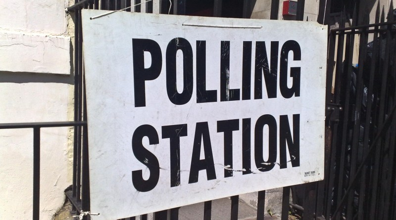 A sign for a Polling Station hung on black wrought iron railings.