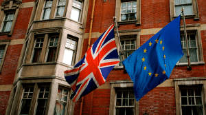 A British flag and EU flag side by side outside a red brick building