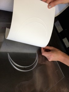 Crescent print and printing plate for Jaynes's The Moon Reader, 2014. Picture shows a translucent printing plate with the image of a crescent moon deeply etched into it. A white piece of paper with the crescent image embossed on it is being peeled away by the disembodied pair of hands of the printer. Her right hand, farthest from the viewer, holds the paper in the upper right corner. Her left hand, close to the viewer, is above the lower right edge of the bottom of the paper still attached to the plate. The reflection of the woman printer, who wears glasses, is seen in the lower edge of the printing plate, which is closest to the viewer. [End of description]