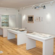 Picture shows exhibition installation shot of Touching the Book: Embossed LIterature for Blind People, taken from the back of the room and facing the exhibition entrance at the further end of the room on the right hand side. The flooring is light wood, and the walls are painted white. The photograph shows three free-standing display cases all containing 4-5 books opened and resting on cradles; two framed items on the right hand side of the wall as well as a large vinyl graphic of Moon's alphabetic system; and information panels are installed on the wall. At the further end of the room, and to the left of the entrance, is a large fixed display cabinet with three shelves holding artifacts (books and a writing frame). To the left of the cabinet is a blank TV screen and below that a table with a red covering that has been laid out with glasses of wine. [end of description]