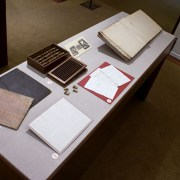 Picture shows the top of a case displaying (left to right) two grooved writing boards in pink and black hues; two letters in manuscript; a box of small blocks with its slatted cover removed and beneath it; a reproduction of an illustration of Victorian writing frames; and an open book with white pages of raised print. The historical materials lie on grey linen.