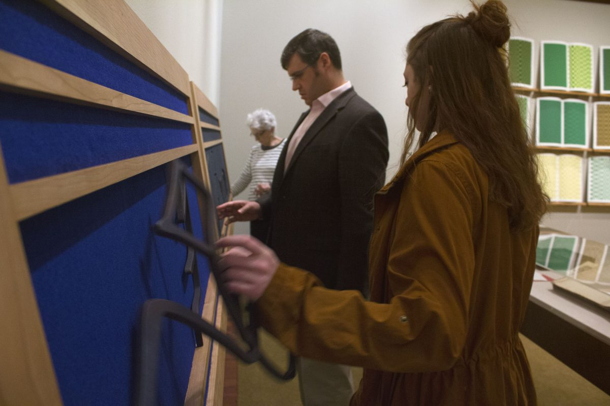 Picture shows a man and woman touching the sculptural letters and two large frames of Gift #2. A woman, with long dark hair and a tan coat, holds a large sculptural letter from the frame closer to the viewer in her left hand. To her right, a man in a grey suit jacket touches the felt covering of the frame farthest from the viewer. In the background, the screen prints of Jaynes's Gift #4 and another woman visitor is visible. [end of description]