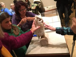 Picture shows exhibition visitors interacting with Teresa Jaynes's Gift #2, a papier mâché owl on a wooden, sideways, cylindrical stand. In the right, the left hand of a man touches the front of the owl. The owl has yellow eyes and tan and white paper feathers. Part of the man's right hand, which holds the top of a cane is also visible. In the left, a woman with long blond hair and wearing a green sweater touches the back of the owl. She stands between a women, with medium-length dark hair and wearing a purple zip-up cardigan, to her left, and the arm of another woman in a red sweater touching the back of the owl, to her right. The woman in purple, who also wears glasses, has her hands in fists and touching. Her knuckles touch in an explanatory gesture. Other gallery visitors walk and look at other parts of the exhibition in the background. [end of description]