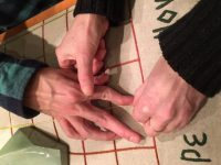 Picture shows the hands of exhibition visitors touching Teresa Jaynes's Gift #5, a tactile map with an embroidered grid and green porcelain geometric shapes representing landforms on a linen background. In the lower right, the hands of a woman, the cuffs of her brown sweater visible, guide the hand of a man over the red threads of the embroidered grid. A part of one of the porcelain landforms is visible in the upper left of the image. [end of description]