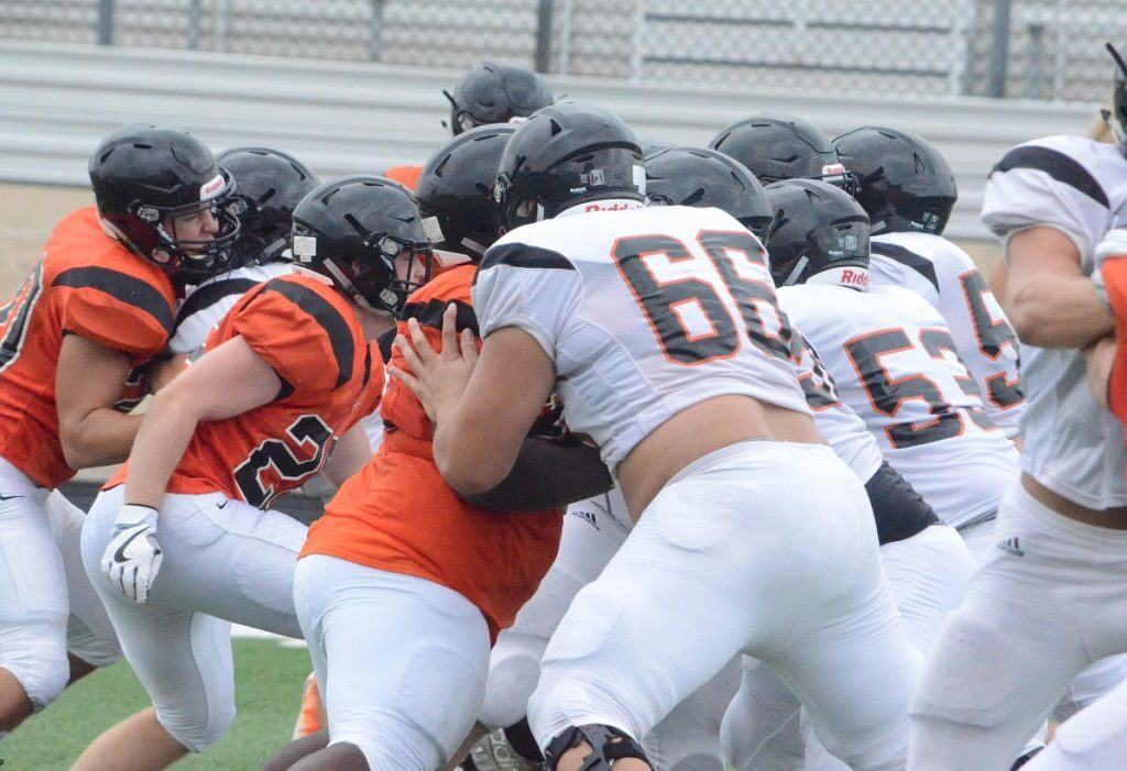 Aledo senior move-in offensive tackle Chuck Filiaga (66) moves the pile on a running play Saturday at Bearcat Stadium during AHS' scrimmage that concluded the first week of practices.