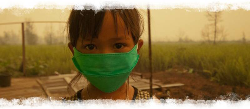 Child wearing mask with wildfire smoke in background
