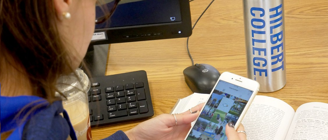 college student in library looking at phone app
