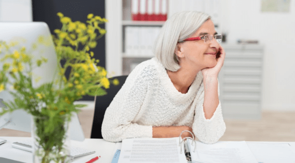 woman in her 60s sitting at desk