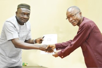 The Vice-Chancellor, Professor Kolawole Salako (left) receiving the Panel's report from the Leader of the accreditation team, Professor Chibueze Ogbonna