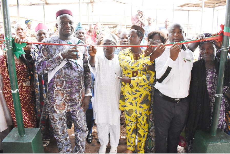 "The Vice-Chancellor, Professor Kolawole Salako, cutting the tape of the newly constructed shed by C:AVA and being assisted by the Deputy Vice-Chancellor (Development), Professor Lateef Sanni, the Lukosi of Ifo Land, Chief Omotola Adebowale and The ""Igbakeji"" Baba Oja, Chief Musiliudeen Aderibigbe."