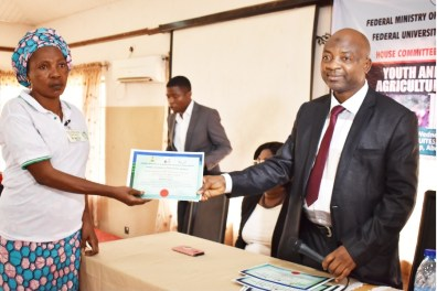 Representative of the Vice-Chancellor, DVC (D), Professor Lateef Sanni presenting a certificate of participation to one of the participants