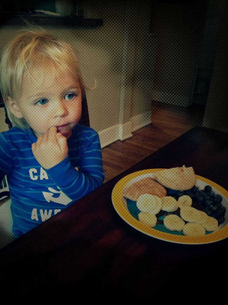 "My son, Rawley, eating breakfast in his ""Captain Awesome"" PJs (""Mini whole wheat pita's stuffed with scrambled eggs, bananas and blueberries.)"