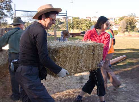 Two gardeners move strawbales to construct the outdoor classroom.