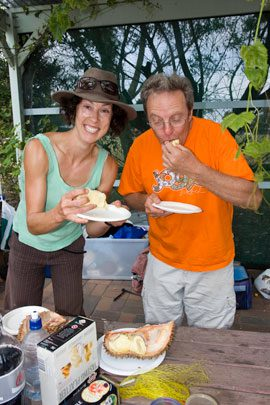 Community gardener Phillip Booth and a fellow gardener take a bite of the spongy and sweet durian.