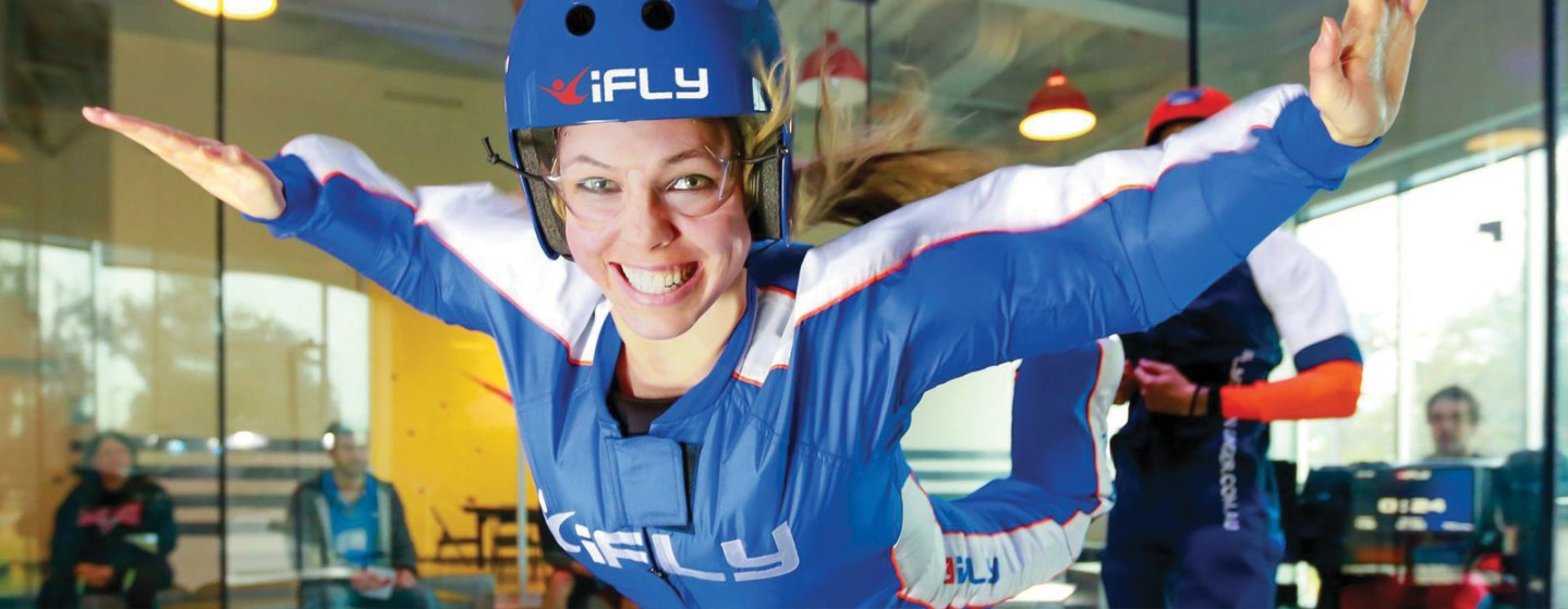 An iFly flight instructor assists a flyer in the wind tunnel. Customers get 60 seconds of flight time.