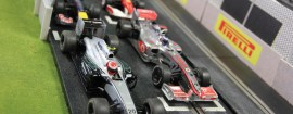 Slot cars modeled after Formula One cars wait at the starting line.