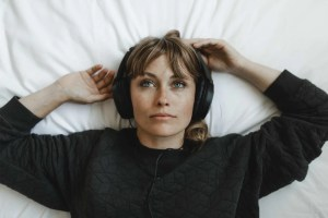 woman listening to music on bed