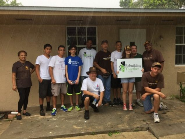 UPS volunteers present check, paint, landscape home of senior