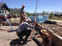 Dusty advises interns Beatrice and Stacey on how to lay the radon tubing to the correct depth.