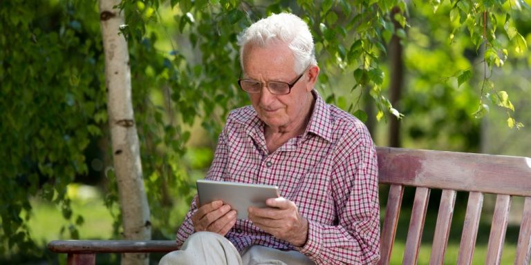 Man sitting on bench in park and looking at computer tablet
