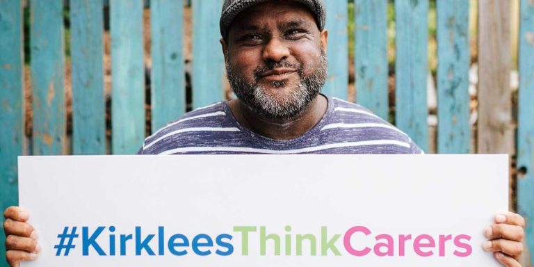 Image show a man holding Kirklees Think Carers sign