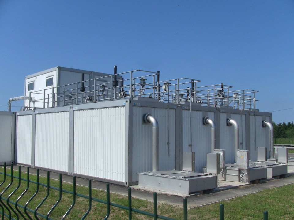 four tank wastewater system behind green metal fence