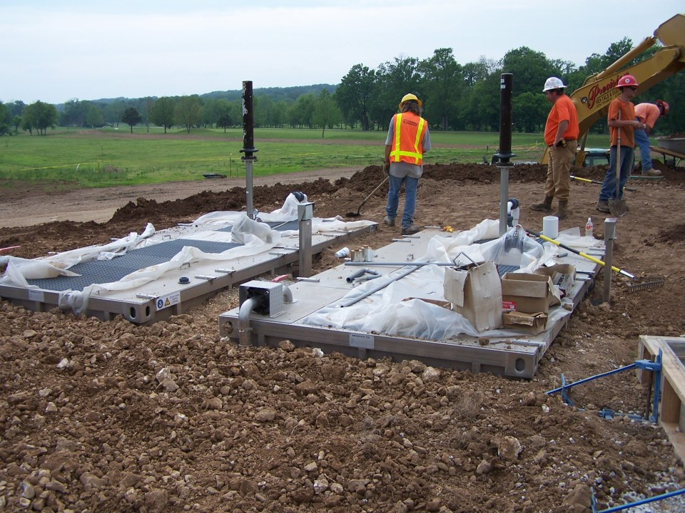 workers grading dirt around two buried wastewater treatment plants