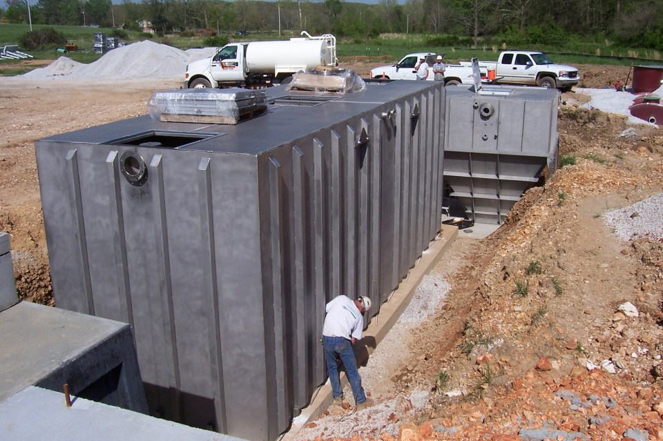 Man working to install small municipal wastewater treatment system