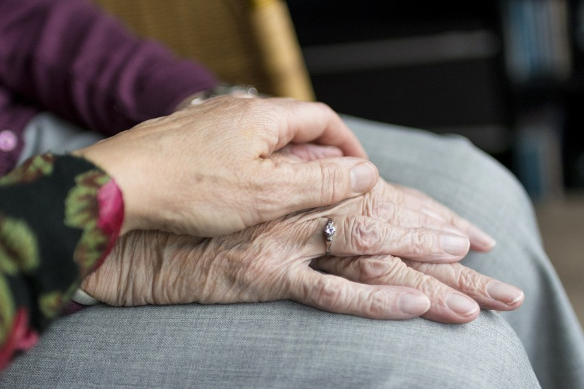 Aged hands on lap with younger hand on top.