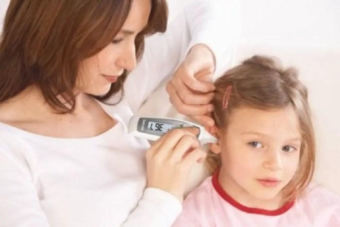 Madre tomando la temperatura a su hija