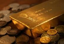 sztaba złota leżąca na złotych monetach