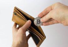 Dłoń wkładająca Bitcoina (BTC) do portfela