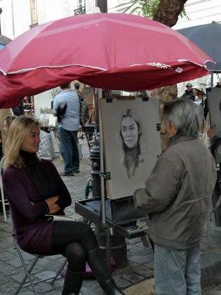 Artista faz o retrato da turista na Place du Tertre