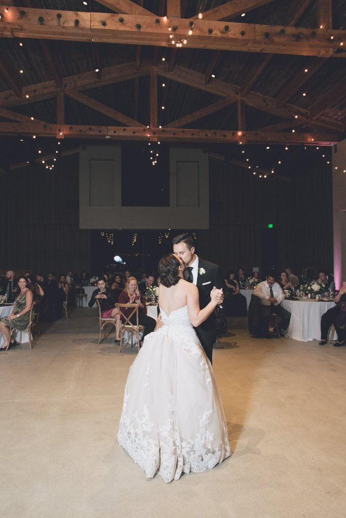 Bride and groom first dance inside the high end barn with market bistro lights for Temecula wedding at wedgewood galway downs wedding venue