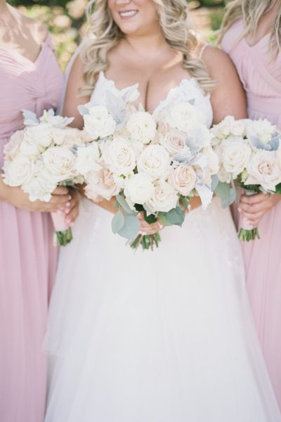 Bride with curled hair style and white and blush bouquet