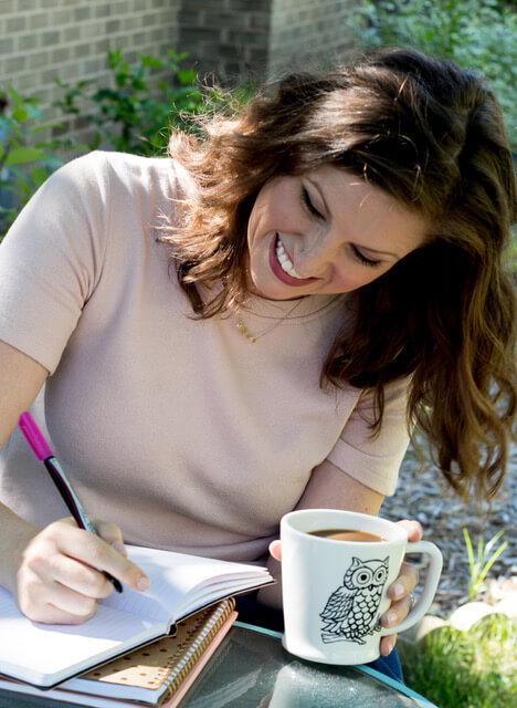 brunette woman, writing in a journal and drinking coffee