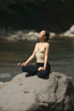 Woman in Lotus Posture on Boulder
