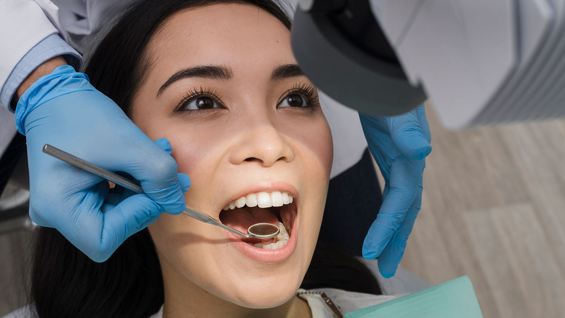 Woman at a dental appointment with the dentist looking in her mouth with a dental hand mirror