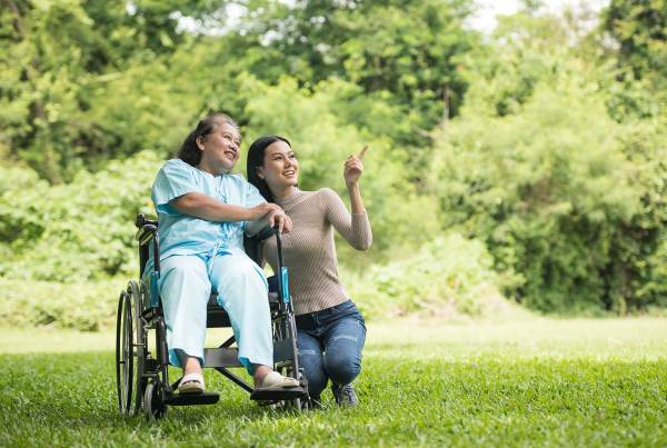 elderly woman in a wheelchair sits and looks into the distance on a field of grass while a young woman crouches besides her and points in the distance