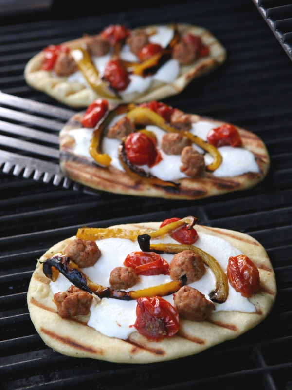Grilled Pizzas with Sausage, Peppers, Roasted Tomatoes and Mozzarella from completelydelicious.com