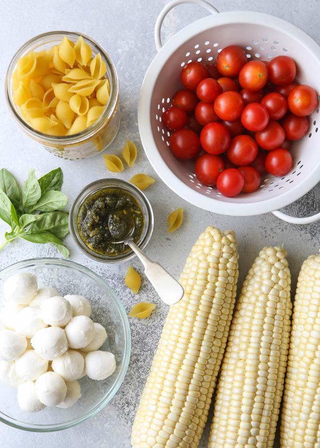 All of the ingredients for fresh corn, tomatoes, pesto and mozzarella salad