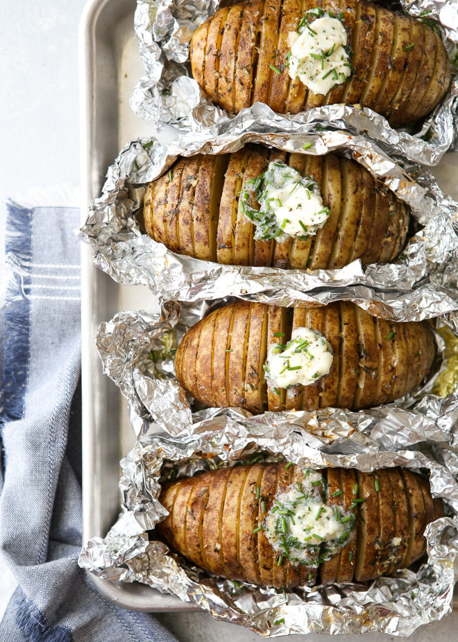 """Baked"" potatoes cooked on the grill and served with chive butter"