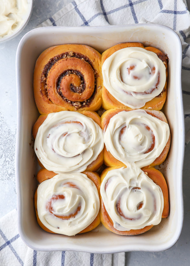Pumpkin cinnamon rolls filled with a pumpkin spice and pecans and topped with a cream cheese frosting