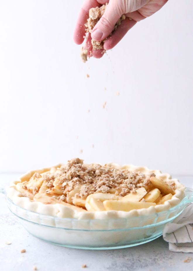 Adding the crumb topping to dutch apple pie