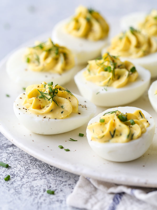 Classic deviled eggs made with mayonnaise, mustard and fresh chives and dill are a simple but irresistible appetizer.