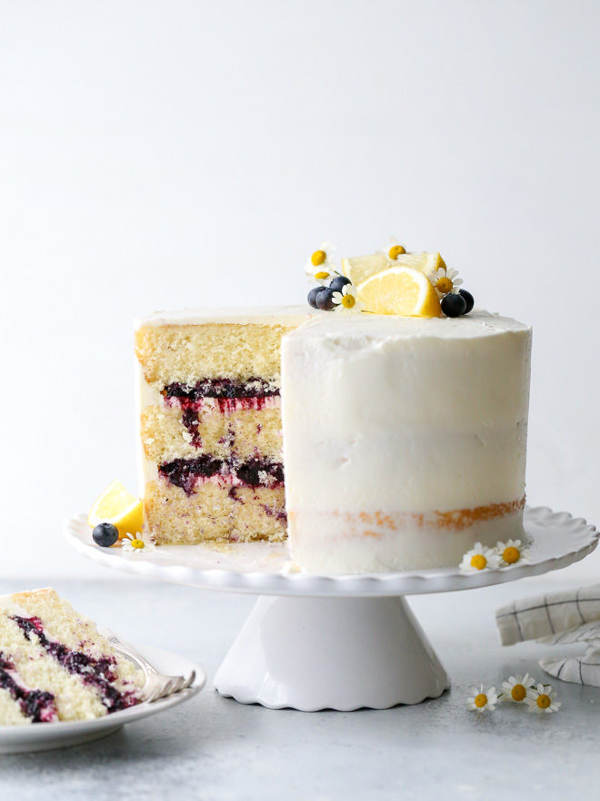 This light and tender lemon blueberry cake is filled with fresh blueberry preserves and frosted with silky lemon buttercream.