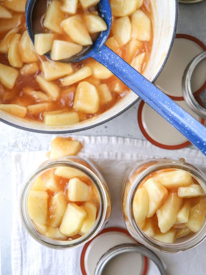 Ladle apple pie filling into jars