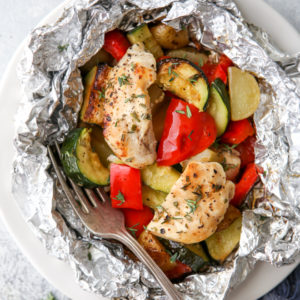 These delicious chicken and veggie tin foil dinners are a complete and hearty meal wrapped up in foil and cooked over a fire, on the grill, or in the oven.